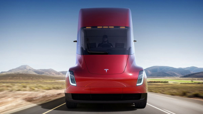 The new red Tesla Semi truck driving on the scenic road