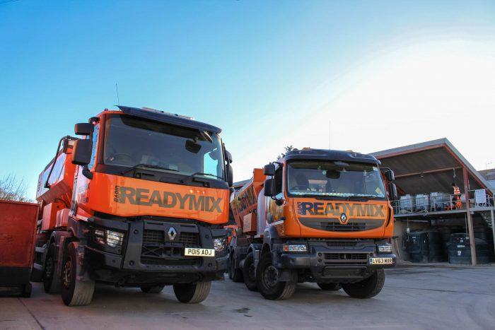 A row of Rapid Readymix trucks on the company yard during the day