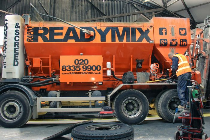 Rapid Readymix engineer is changing tires and checking safety on one of the orange vehicles